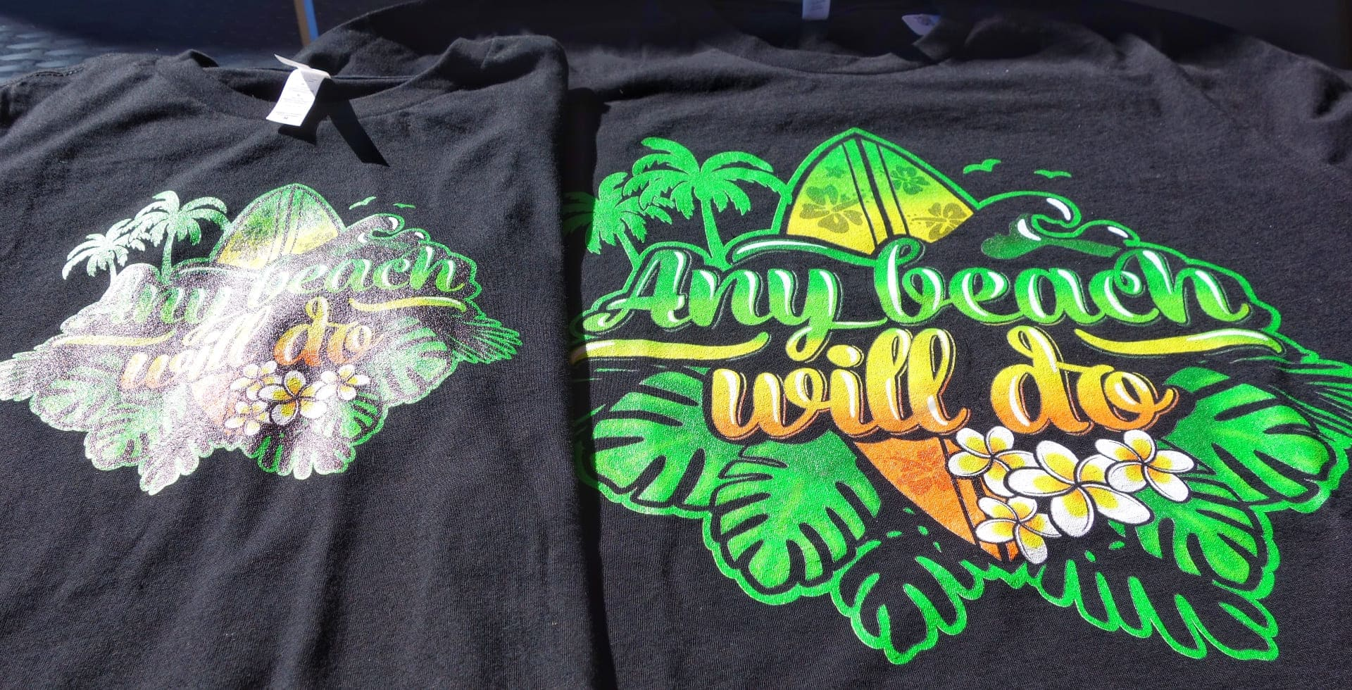 Two black t-shirts with a beach print on