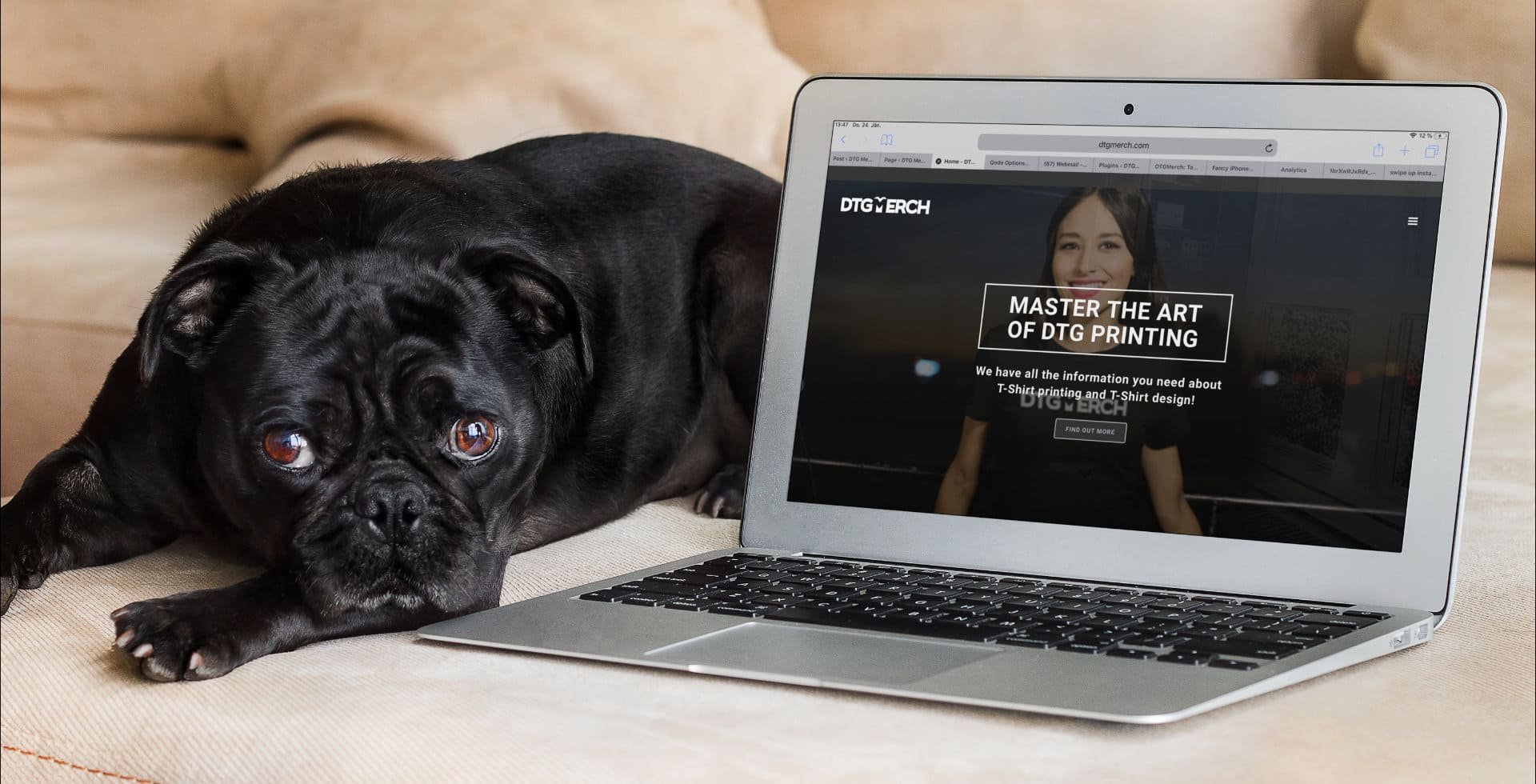 Black dog next to a lap top computer. On screen, the DTG Merch blog page.