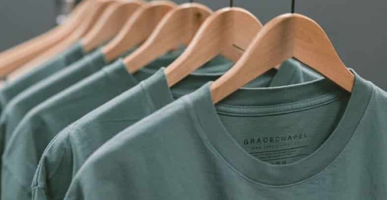 Green t-shirts on a hanger.