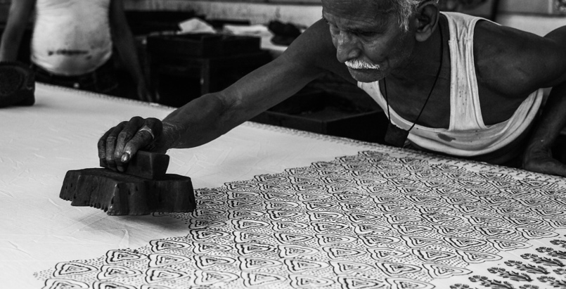 An old man decorating white fabric with block printing technique.
